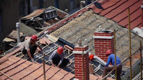 builder repair roof under burning sun Stock Video Footage