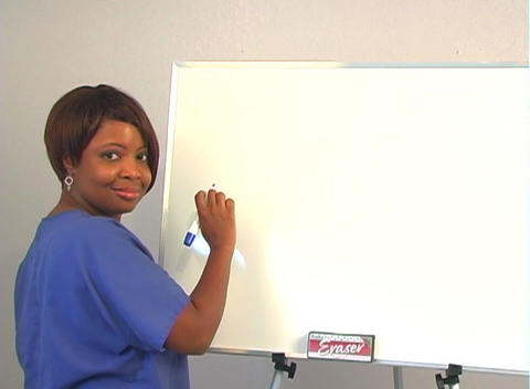 """Beautiful Nurse Writes """"C-Section"""" on a White Board Stock Video Footage"""