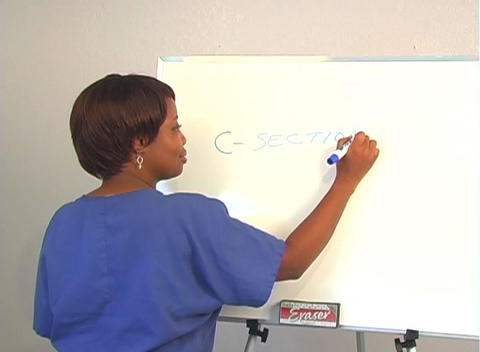 "Beautiful Nurse Writes ""C-Section"" on a White Board Stock Video Footage"
