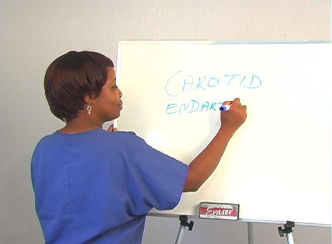 "Beautiful Nurse Writes ""Carotid Endarterectomy"" on a White Board Footage"