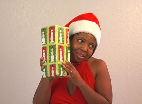 Beautiful Woman Shakes a Christmas Gift (3) Footage
