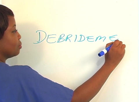 "Beautiful Nurse Writes ""Debridement"" on a White Board (close-up) Footage"