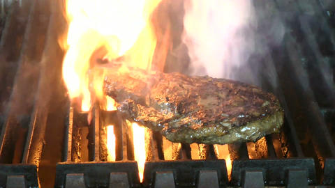 Delicious juicy rib eye steak on a grill with flam Stock Video Footage