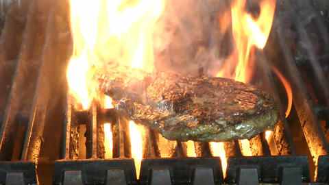 Delicious juicy rib eye steak on a grill with flam Footage