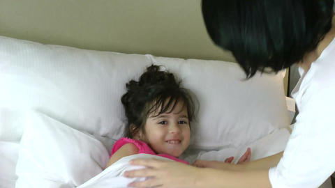 Mother tucking her daughter in to bed Stock Video Footage