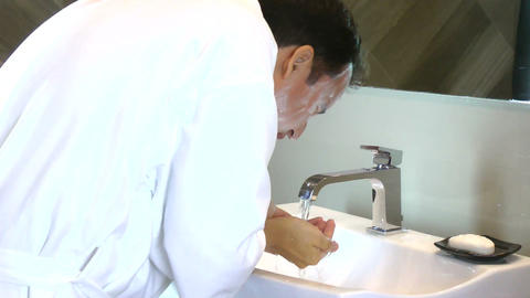 Young man washing his face in sink Footage