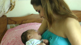 Mother consoling a crying newborn baby in her bedr Footage