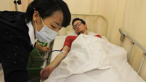 Asian Nurse Attending To Foreign Patient stock footage
