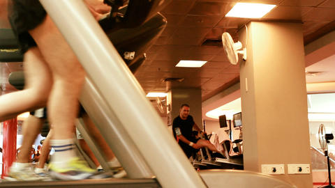 people at the gym exercising on a cross trainer Tr Footage