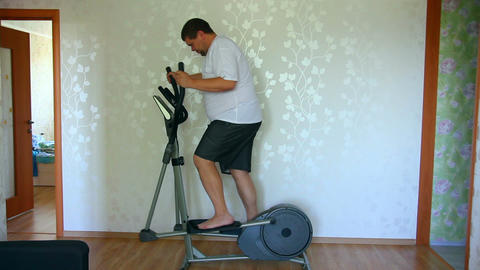 overweight man exercising on trainer ellipsoid Stock Video Footage