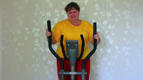 overweight woman exercising on trainer ellipsoid Stock Video Footage