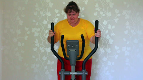 overweight woman exercising on trainer ellipsoid - Stock Video Footage