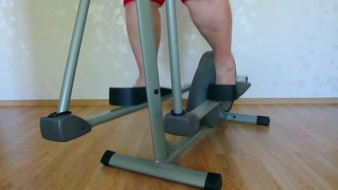overweight woman legs exercising on trainer ellips Stock Video Footage