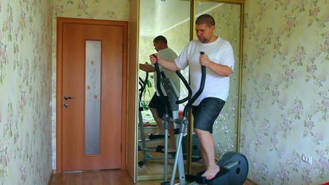 overweight man exercising on trainer ellipsoid - t Footage