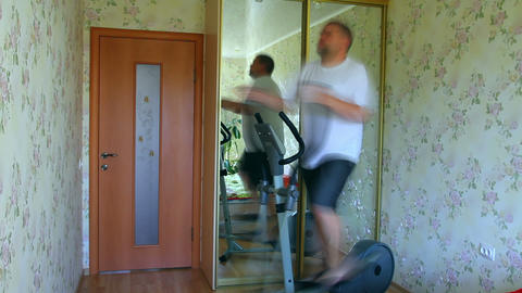 overweight man exercising on trainer ellipsoid - t Stock Video Footage