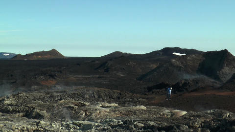 Tourist walking trough volcanic area in Iceland Stock Video Footage