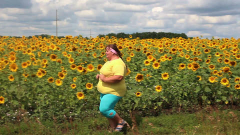 fitness - overweight woman running along field of Stock Video Footage