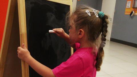 little girl drawing sun with chalk on blackboard Stock Video Footage