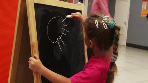 little girl drawing sun with chalk on blackboard Footage