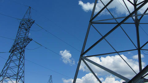 tall electric masts against cloudy sky - zoom time Stock Video Footage