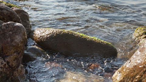 Water waves between stones on the sea beach Stock Video Footage
