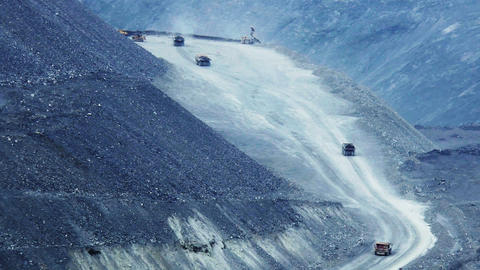Heavy mining dump trucks moving along the opencast Stock Video Footage