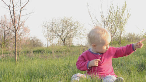 Baby sits on a grass, dolly shot Stock Video Footage