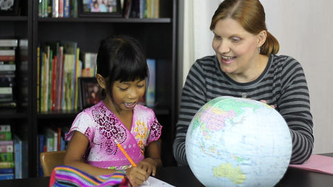 Homeschool Mom Teaching Asian Daughter Geography stock footage