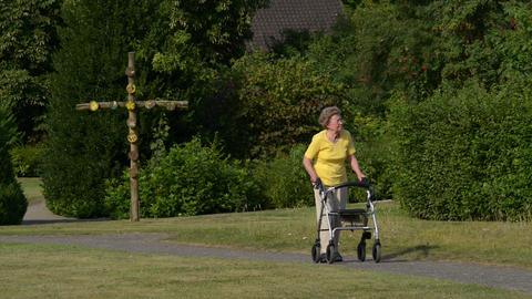 retiree pensioner walk with rollator in park 11074 Stock Video Footage