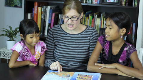 Homeschool Mom Reading To Daughters During School Stock Video Footage