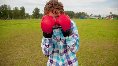 The boy in boxing gloves in a meadow Footage