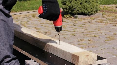 Carpenter using a screw gun to fasten screw into a Stock Video Footage