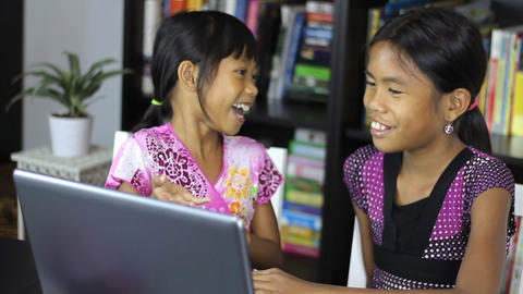 Two Asian Sisters Working On A Laptop Computer Stock Video Footage
