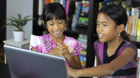 Two Asian Sisters Working On A Laptop Computer Footage