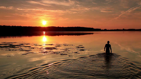 Man Enters The Lake At Sunset stock footage