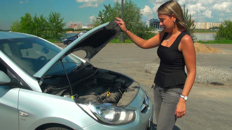 Blonde opens the hood of a car Stock Video Footage