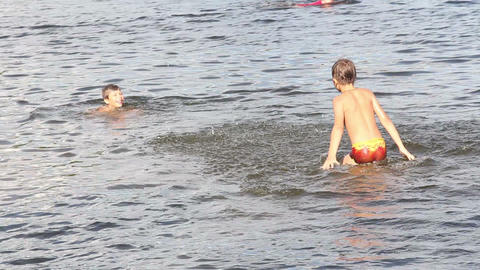 Two boys swimming in the river Stock Video Footage