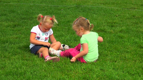 Two little girls playing in the grass Stock Video Footage