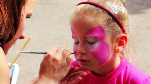 artist paints on face of little girl Stock Video Footage