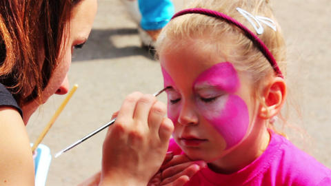 artist paints on face of little girl Footage