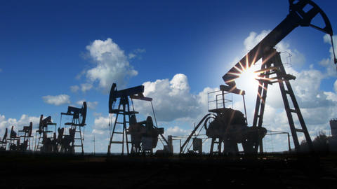 working oil pumps silhouette against timelapse clo Stock Video Footage