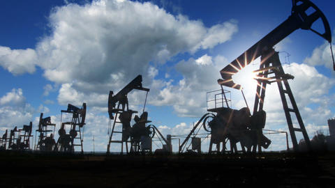 working oil pumps silhouette against timelapse clo Footage