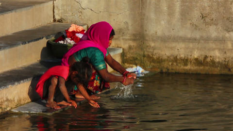 Indian woman with her daughter to wash clothes in Stock Video Footage