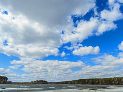 Clouds over the lake. Last snow. Time Lapse Footage