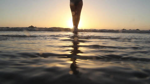 Beautiful female legs in the surf at sunset Stock Video Footage