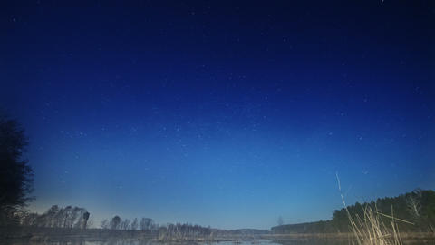 Sunset and starry sky reflected in lake Stock Video Footage