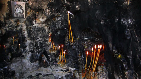 Christian holy place - icon and candles in grotto Stock Video Footage