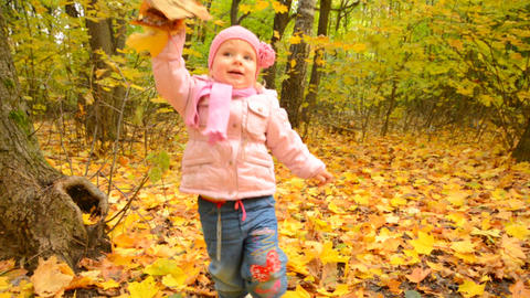 Cute Little Baby Girl is Playing with Yellow Leafs Footage