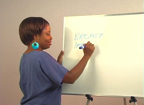 "Beautiful Nurse Writes ""Breast Implants"" on a White Board Stock Video Footage"