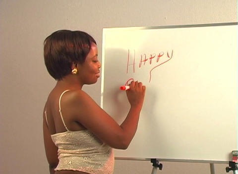 """Sexy woman writes """"Happy Birthday Handsome"""" on a white board Stock Video Footage"""